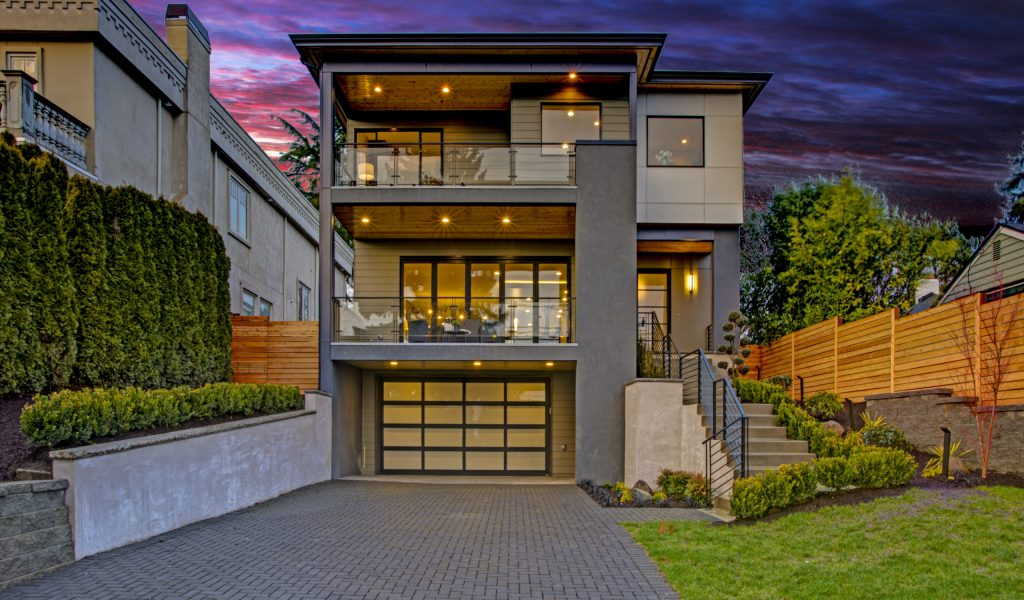Luxury modern home exterior at sunset boasts four car garage with wide driveway.